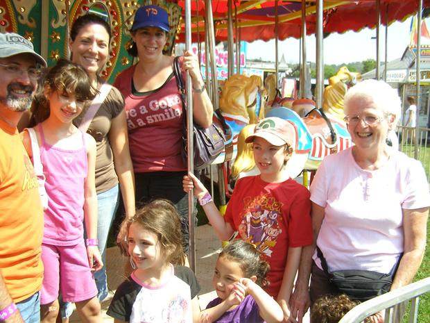 A family enjoys the carousel at the GDS Greene Dreher Sterling Fair in Newfoundland Wayne County Pennsylvania in the Pocono Mountains